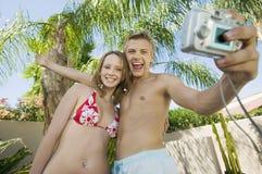Jeunes couples adoptant à photo de lui-même la position d'angle faible Images stock