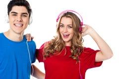 Jeunes couples adorables appréciant la musique Image stock
