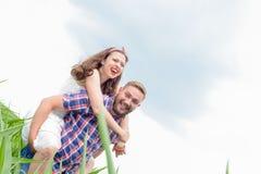 Jeunes couples adultes affectueux heureux passant le temps sur le champ le jour ensoleillé Image stock