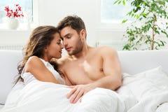 Jeunes couples adultes dans la chambre à coucher Images stock
