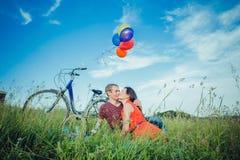 Jeunes couples adultes heureux dans l'amour sur le champ Deux, homme et femme ont le pique-nique, souriant et se reposant sur l'h Photos libres de droits