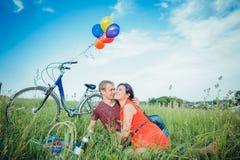 Jeunes couples adultes heureux dans l'amour sur le champ Deux, homme et femme ont le pique-nique, souriant et se reposant sur l'h Photos stock