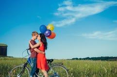 Jeunes couples adultes heureux dans l'amour sur le champ Deux, homme et femme souriant et se reposant après l'équitation de vélo Photos stock