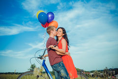 Jeunes couples adultes heureux dans l'amour sur le champ Deux, homme et femme souriant et se reposant après l'équitation de vélo Images libres de droits