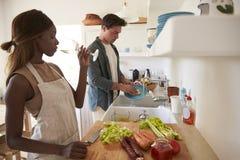 Jeunes couples adultes préparant la nourriture et buvant du vin Image stock