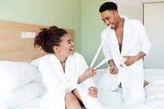 Jeunes couples affectueux africains de sourire se reposant sur le lit Photographie stock