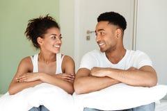 Jeunes couples affectueux africains de sourire se reposant sur le lit Image stock