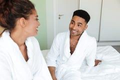Jeunes couples affectueux africains de sourire se reposant sur le lit Photo libre de droits