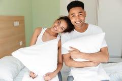 Jeunes couples affectueux africains gais se reposant sur le lit Photos libres de droits