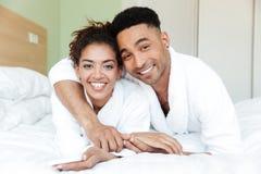 Jeunes couples affectueux africains heureux sur le lit Images stock
