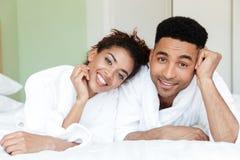 Jeunes couples affectueux africains heureux sur le lit Photographie stock libre de droits