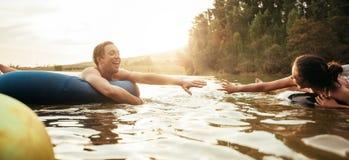 Jeunes couples affectueux ayant l'amusement dans le lac images stock