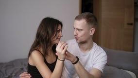 Jeunes couples affectueux détendant sur le lit à la maison, se touchant mains, regardant dans les yeux frottant la caresse, appré banque de vidéos