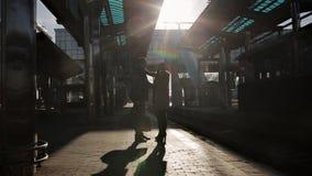 Jeunes couples affectueux d'adieu sur la plate-forme de la gare ferroviaire dans la dernière lumière du soleil Silhouettes de jeu banque de vidéos