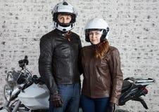 Jeunes couples affectueux dans un équipement et des casques de moto se tenant ensemble près de la motocyclette de rue dans le gar images stock