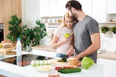 Jeunes couples affectueux de sourire se tenant à la cuisine et à la cuisson Photos stock
