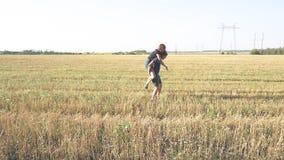 Jeunes couples affectueux en nature en été sur un fond de champ avec l'avoine banque de vidéos