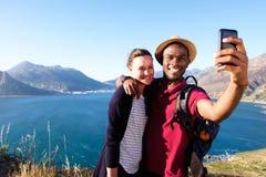 Jeunes couples affectueux en vacances prenant le selfie Image stock