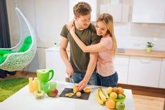 Jeunes couples affectueux faisant cuire les fruits organiques pour le jus à la table Nourriture saine Famille heureux Consommatio photos stock