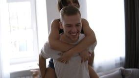 Jeunes couples affectueux Femme de brune dans des vêtements domestiques étreignant l'homme de sa de retour détente appréciant des clips vidéos