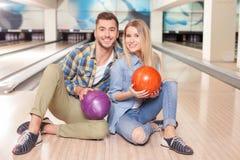 Jeunes couples affectueux gais dans le club kegling Photo libre de droits