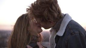 Jeunes couples affectueux gais et blondy appréciant un baiser romantique tout en se tenant sur le haut toit venteux avec urbain banque de vidéos
