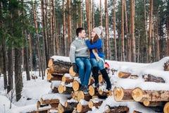 Jeunes couples affectueux habillés dans le chandail bleu se reposant sur le bois de chauffage et étreignant dans la forêt d'hiver images libres de droits