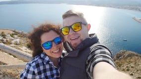 Jeunes couples affectueux heureux prenant le selfie sur des montagnes près de la mer banque de vidéos