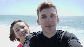 Jeunes couples affectueux heureux souriant dans la cam?ra en mode de selfie sur la plage rocheuse Vagues fortes frappant les roch clips vidéos