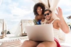 Jeunes couples affectueux heureux utilisant l'instrument tout en se reposant sur la station de vacances Photos libres de droits