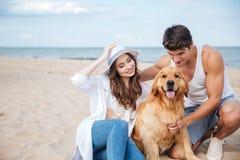 Jeunes couples affectueux jouant avec leur chien au bord de la mer Photographie stock