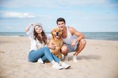 Jeunes couples affectueux jouant avec leur chien au bord de la mer Images libres de droits