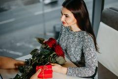 Jeunes couples affectueux la date, homme donnant les roses et le cadeau à son gi Photo stock