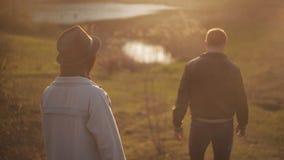 Jeunes couples affectueux marchant en parc au coucher du soleil Une fille saute au dos de son amant et le type la porte vers le b banque de vidéos