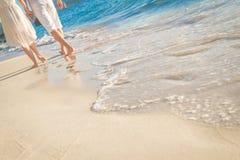 Jeunes couples affectueux marchant par la plage tropicale Photos stock
