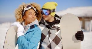 Jeunes couples affectueux posant avec des surfs des neiges Images stock