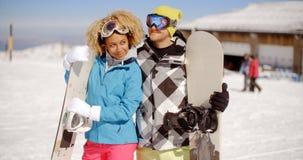 Jeunes couples affectueux posant avec des surfs des neiges Photographie stock libre de droits
