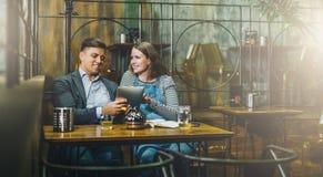Jeunes couples affectueux se reposant en café à la table et à l'aide de la tablette La fille et le type utilisent l'instrument nu Images stock