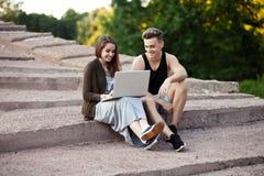 Jeunes couples affectueux se reposant sur une promenade avec l'ordinateur portable photos stock
