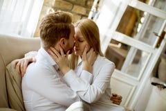 Jeunes couples affectueux sur le sofa images stock