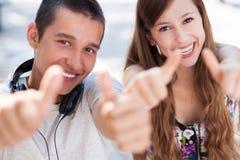 Jeunes couples affichant des pouces vers le haut Image stock