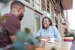 Jeunes couples africains parlant ensemble à une table de café de trottoir Photos libres de droits