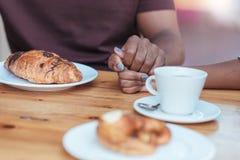 Jeunes couples africains romantiques tenant des mains à un café de trottoir Photo libre de droits