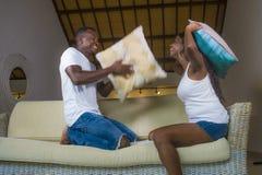 Jeunes couples afro-américains romantiques attrayants et heureux dans l'amour espiègle au divan de salon jouant apprécier de comb images libres de droits