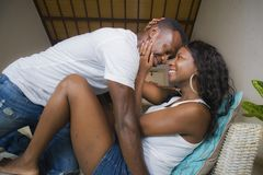 Jeunes couples afro-américains romantiques attrayants et heureux dans la caresse espiègle menteuse d'amour au divan de salon joua image libre de droits