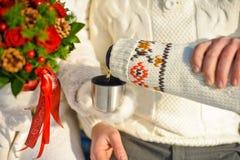jeunes couples aimés se chauffant en parc d'hiver mains avec des tasses de thé chaud Photo libre de droits