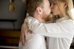Jeunes couples aimants embrassant dans la chambre photos stock