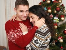 Jeunes couples ainsi que l'arbre de Noël dans l'intérieur à la maison - concept d'amour et de vacances, la veille de Noël Photographie stock libre de droits