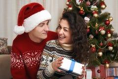 Jeunes couples ainsi que l'arbre de Noël et cadeaux dans l'intérieur à la maison - concept d'amour et de vacances, la veille de N Photos stock