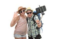 Jeunes couples américains attrayants et chics prenant la photo de selfie avec le téléphone portable d'isolement sur le blanc Photographie stock libre de droits